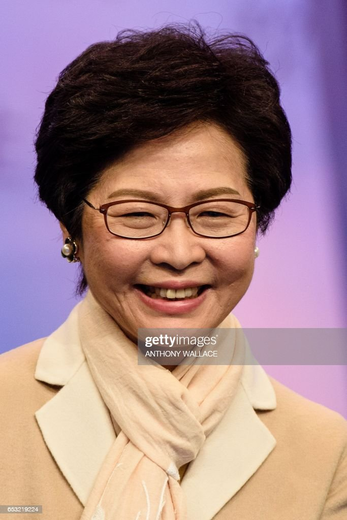Hong Kong leadership candidate Carrie Lam arrives at a studio before facing off with John Tsang and ex-judge Woo Kwok-hing in their first televised debate in Hong Kong on March 14, 2017. Hong Kong's three leadership candidates faced off in their first televised debate on March 14 as criticism mounts over a voting process which favours Beijing and bypasses the majority of the electorate. / AFP PHOTO / Anthony WALLACE