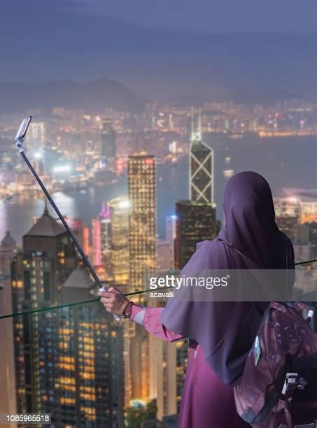 hong kong. donna musulmana che si fa un selfie. - velo foto e immagini stock