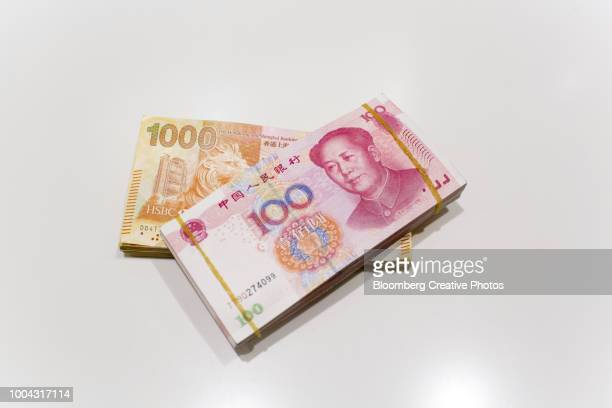 hong kong one thousand dollar banknotes and chinese one hundred yuan banknotes - chinese currency stock pictures, royalty-free photos & images