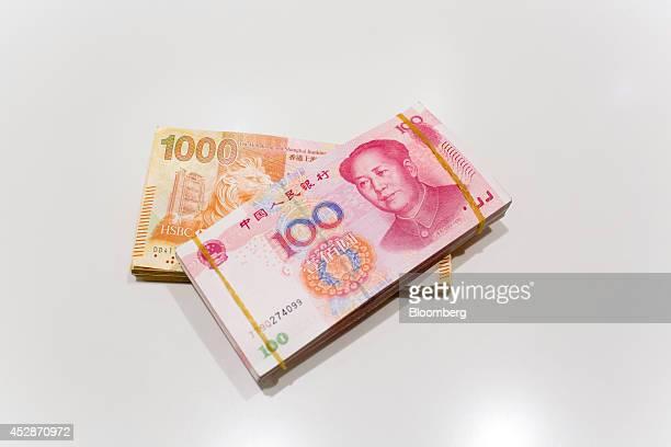 Hong Kong one thousand dollar banknotes and Chinese one hundred yuan banknotes are arranged for a photograph at a Hang Seng Bank Ltd branch in Hong...