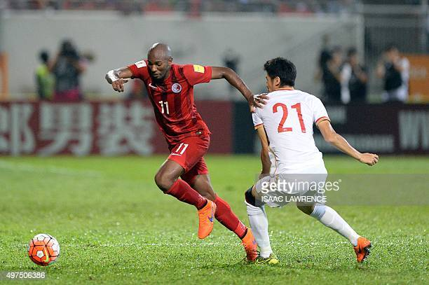 Hong Kong player Alessandro Ferreira Leonardo dribbles the ball past Chinese player Yu Hai during a world cup qualifier at Mong Kok stadium in Hong...