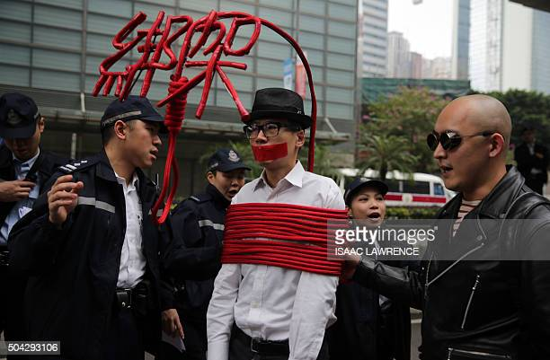 Hong Kong police as a protester wrapped up with a rope made into a noose to move on during a protest march calling for the release of missing...