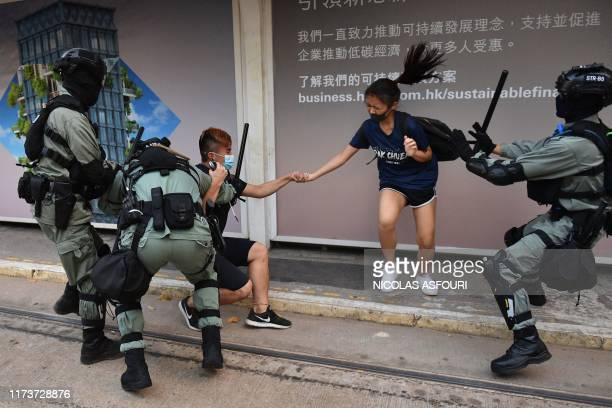 TOPSHOT Hong Kong police chase down a couple wearing facemasks in the Central district in Hong Kong on October 5 a day after the city's leader...