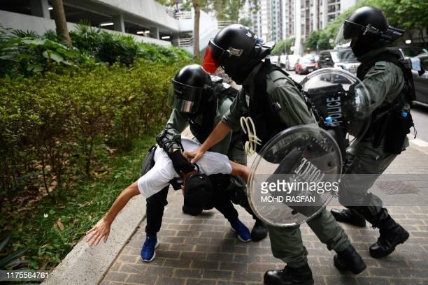 Hong Kong police detain a man for an unknown reason outside a shopping centre in the Tai Koo area of Hong Kong on October 13 2019 Hong Kong riot...