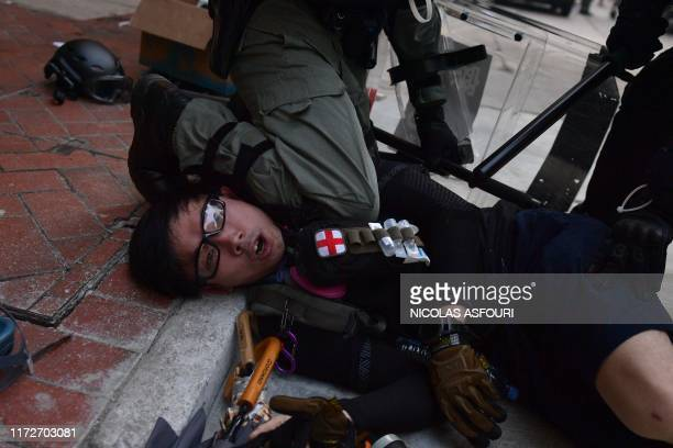 TOPSHOT Hong Kong police detain a protester during demonstrations in the Wanchai district in Hong Kong on October 1 as the city observes the National...