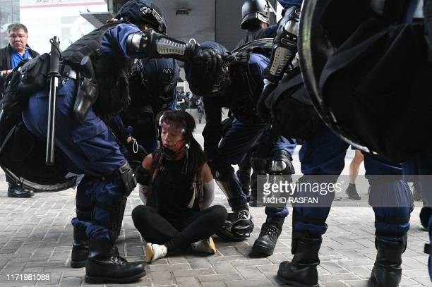 TOPSHOT Hong Kong police detain a woman near the central government offices after thousands took part in an unsanctioned march through Hong Kong on...