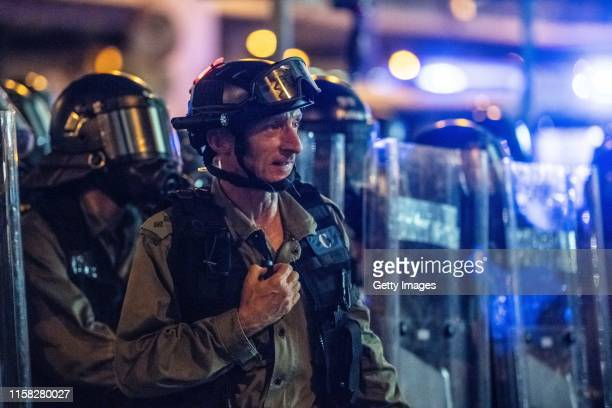 Hong Kong police officer David Jordan stands in front of a line of riot police during a demonstration in the area of Sheung Wan on July 28 2019 in...