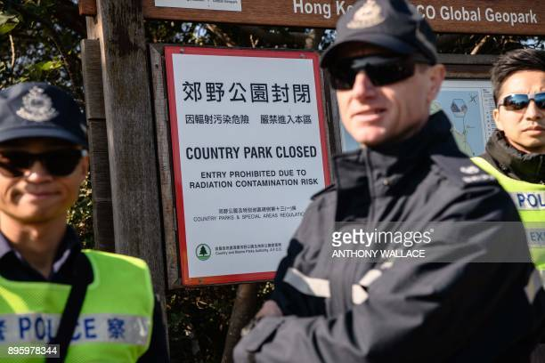 Hong Kong Police stand in front a country park closure notice due to radiation contamination as part of an interdepartmental Daya Bay Contingency...