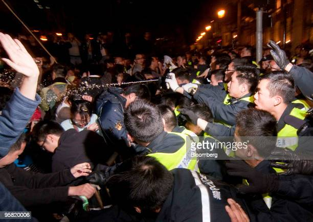 A Hong Kong policeman pepper sprays demonstrators during a protest outside the Legislative Council building in Hong Kong China on Saturday Jan 16...
