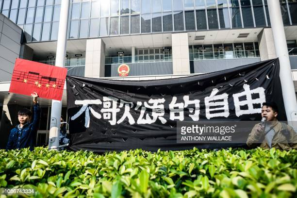 Hong Kong pro-democracy activist Joshua Wong holds up a placard depicting part of the musical score of the Chinese national anthem as he stands next...