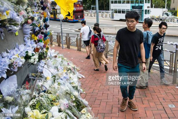 Hong Kong pro-democracy activist Joshua Wong , who was just released from jail, walks past flower tributes at a makeshift memorial site for a...
