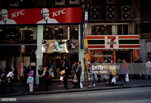 Hong Kong residents wait for buses outside a KFC fast food restaurant and 7Eleven store
