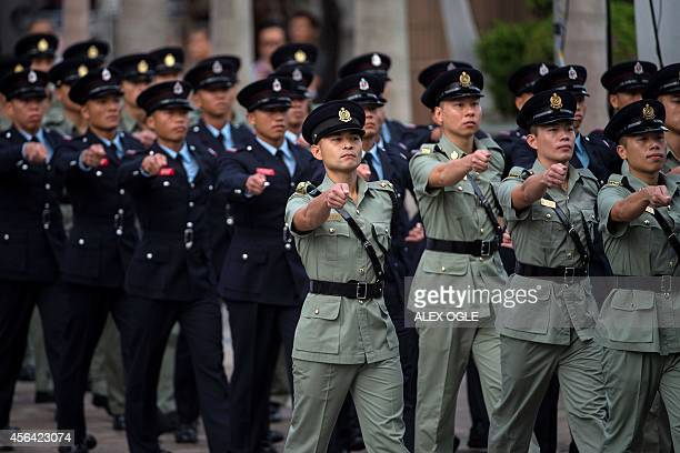 Hong Kong security forces march at a flag raising ceremony to mark the 65th anniversary of the founding of Communist China in Hong Kong on October 1...