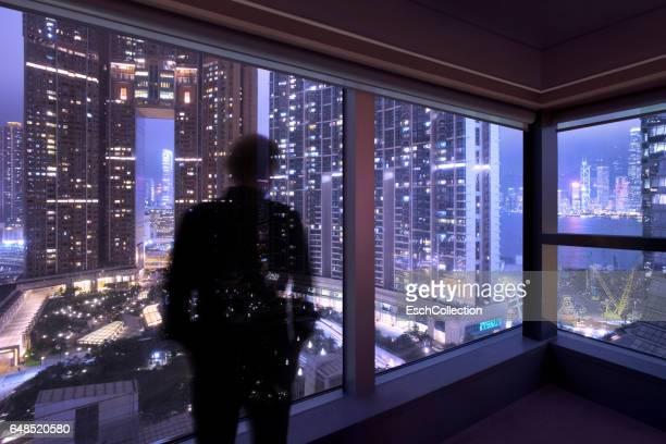 Hong Kong, silhouette of man looking through window at skyline