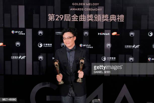 Hong Kong singer Eason Chan holds his trophies after winning the Best Male Vocalist Mandarin and Album of the Year awards during the 29th Golden...