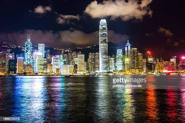 Hong Kong skyline by night. Shiny lights over water, nice clouds and skycrapers.