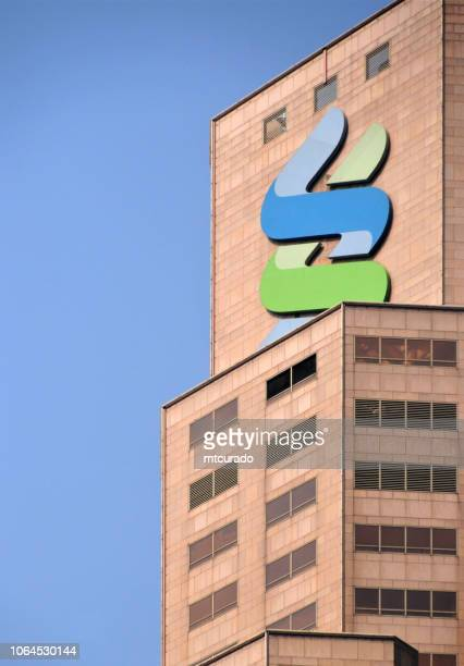 hong kong: standard chartered bank with logo at the top of the skyscraper - standard chartered bank stock pictures, royalty-free photos & images