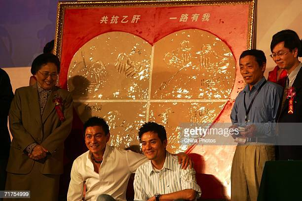 Hong Kong star Andy Lau poses for pictures with a fan during a promotion to fight Hepatitis B on August 30 2006 in Beijing China Andy Lau was...