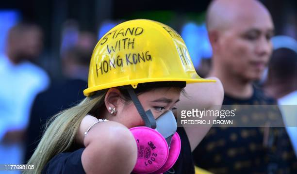 A Hong Kong supporter adjusts her mask outside Staples Center ahead of the Lakers vs Clippers NBA season opener in Los Angeles on October 22 2019...