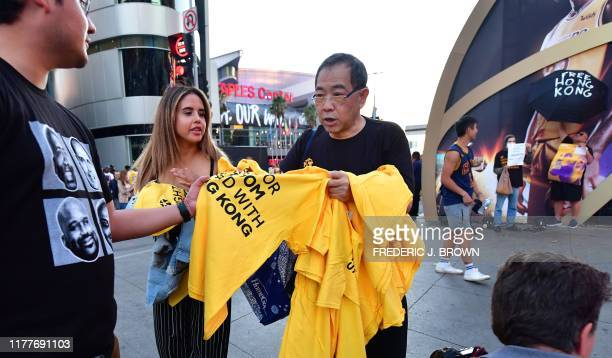 Hong Kong supporters distribute free tshirts outside the Staples Center ahead of the Lakers vs Clippers NBA season opener in Los Angeles on October...