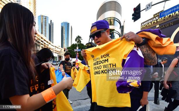 Hong Kong supporters hand out free tshirts outside Staples Center ahead of the Lakers vs Clippers NBA season opener in Los Angeles on October 22 2019...