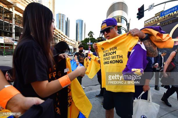 Hong Kong supportes distribute free tshirts outside the Staples center ahead of the Lakers vs Clippers NBA season opener in Los Angeles on October 22...