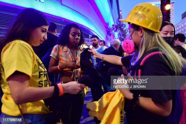 Hong Kong supportes hold distribute free tshirts outside the Staples center ahead of the Lakers vs Clippers NBA season opener in Los Angeles on...