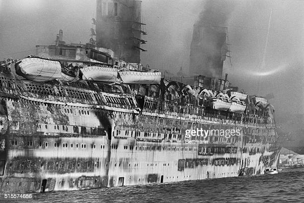 The gutted hull of the former Queen Elizabeth is twisted and charred early 1/10 as the ship lies at anchor in the aftermath of a diastrous fire that...