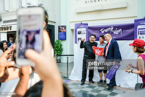 Hong Kongbased Kim JungUn impersonator Howard X and Trump lookalike Dennis Alan seen having photos taken with the singaporean locals as the real US...