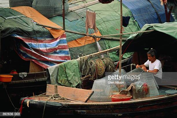 hong kong,causeway bay, man mending fishing basket on junk boat - 20th century stock pictures, royalty-free photos & images