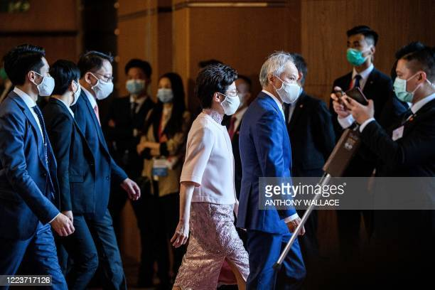 Hong Kong's Chief Executive Carrie Lam leaves with her husband Lam Siu-por following a flag-raising ceremony to mark the 23rd anniversary of Hong...