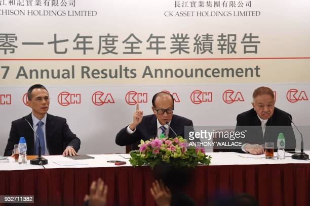 Hong Kong's richest man Li Kashing gestures as he speaks between his son Victor and CK Hutchison comanaging director Canning Fok during a press...