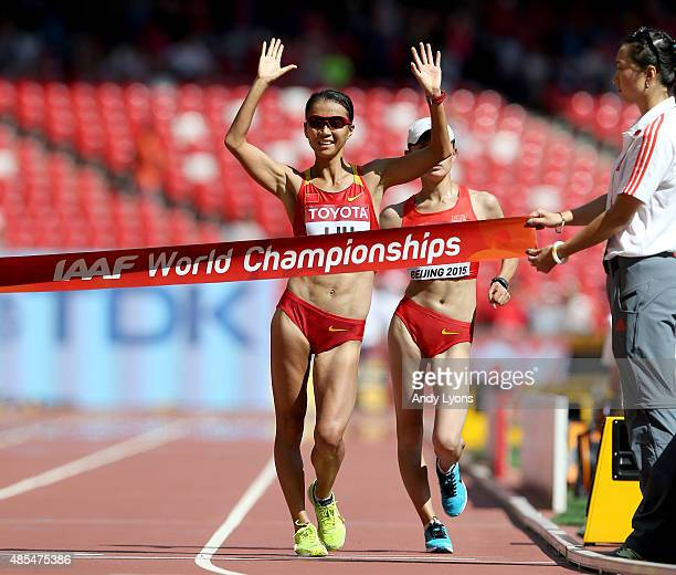 Hong Liu of China crosses the finish line to win gold ahead of Xiuzhi Lu of China in the Women's 20km Race Walk final during day seven of the 15th...
