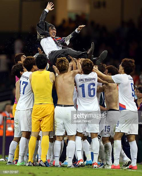 Hong Myung Bo coach of Korea is lifted up as they celebrate their victory over Japan during the Men's Football Bronze medal playoff match between...