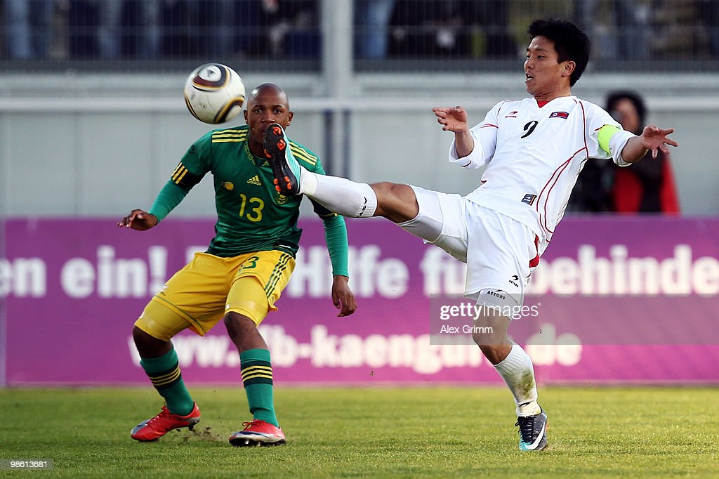 Hong Yong Jo (front) of North Korea shoots the ball ahead of Andile Jali of South Africa during the international friendly match between South Africa and North Korea at the Brita arena on April 22, 2010 in Wiesbaden, Germany.