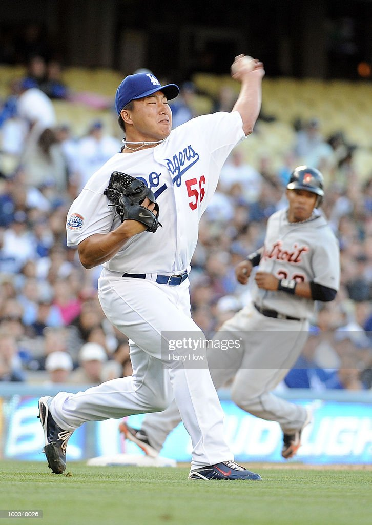 Hong-Chih Kuo #56 of the Los Angeles Dodgers makes a throw to first for the third out with the bases loaded in front of Ramon Santiago #39 of the Detroit Tigers during the seventh inning at Dodger Stadium on May 22, 2010 in Los Angeles, California.