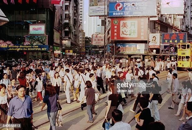 Hongkong Menschenmassen beim Überqueren einer Straßenkreuzung im Zentrum der Metropole Häuserfluchten und Reklametafeln prägen das Bild des...