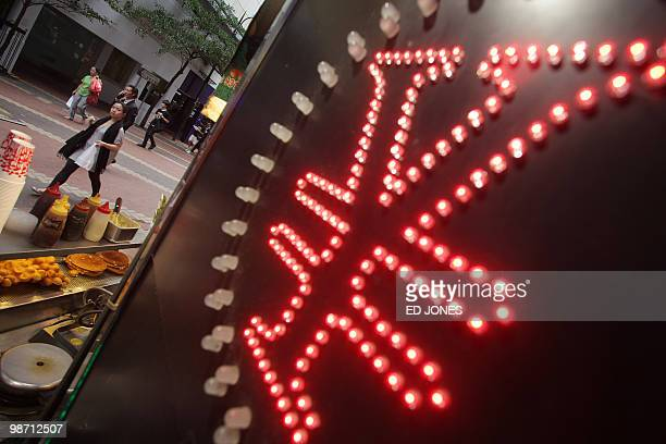 HongKongChinaUSeconomycurrencytradingfinanceFOCUS by Peter Brieger People walk down a street past a Chinese yuan sign at a currency exchange shop in...