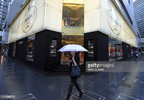 HongKongItalyluxuryfashionIPOPradaADVANCER by Peter Brieger A woman walks past a Prada shop on a rainy afternoon in Hong Kong on June 22 2011 Italian...