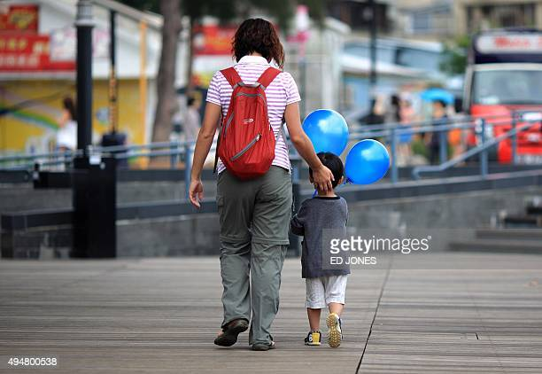 STORY 'HongKonglifestyleeducationparentingFEATURE' by Judith Evans A woman walks with a child holding balloons in Hong Kong on June 4 2011 Since Amy...