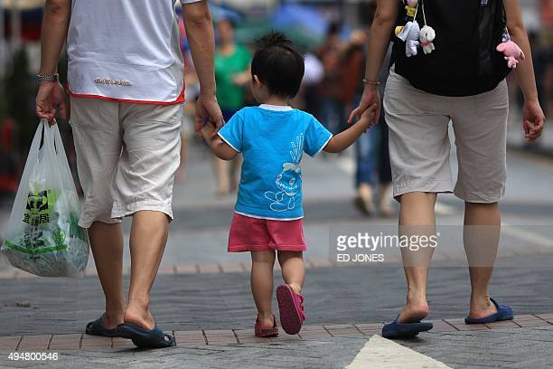 STORY 'HongKonglifestyleeducationparentingFEATURE' by Judith Evans Parents gold the hands of their child as they walk in Hong Kong on June 4 2011...