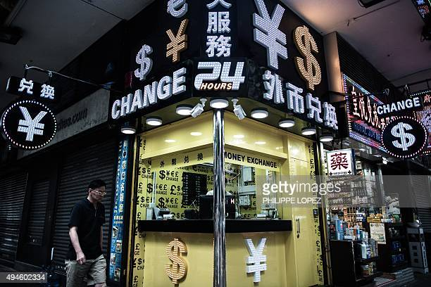 HongKongUSeconomypropertyFOCUS by Dennis CHONG This picture taken on August 13 2015 shows a pedestrian walking past an currency exchange booth in...