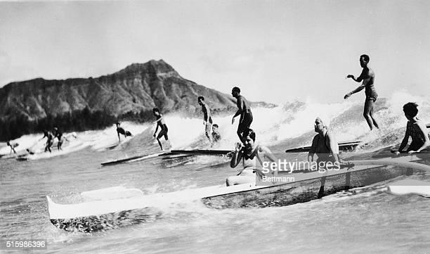 Honolulu, Hawaii. Outrigger canoe and surfers on wave, Waikiki Beach.