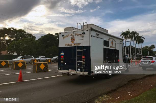 A Honolulu police vehicle enters the Nimitz Gate entrance to the Pearl Harbor Naval Shipyard to assist with a fatal shooting incident in Honolulu...