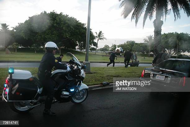 A Honolulu Police Officer stops to help after three or more motorcycle police officers crashed while escorting US President George W Bush's motorcade...