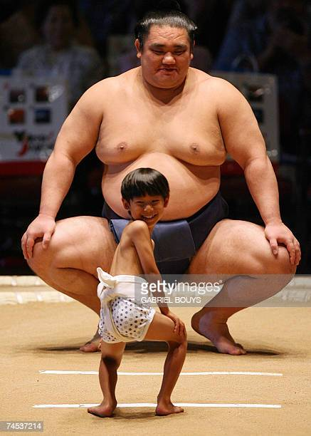 A young boy laughs as he lines up against a professional sumo wrestler during an exhibition before the start of the second day of the Grand Sumo...