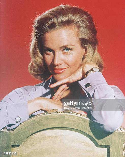Honor Blackman British actress posing in a studio portrait aginst a red background issued as publicity for the film 'Goldfinger' circa 1964 The James...