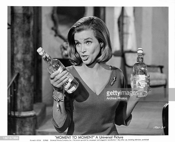 Honor Blackman holding bottles of vodka in a scene from the film 'Moment To Moment', 1965.