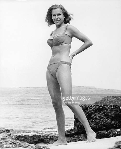 Honor Blackman standing on the beach wearing a bikini in a scene from the film 'Goldfinger' 1964