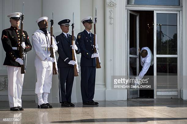 Honor guard wait as a staff member cleans a door at the White House before greeting guests for a group dinner during the US Africa Leaders Summit...